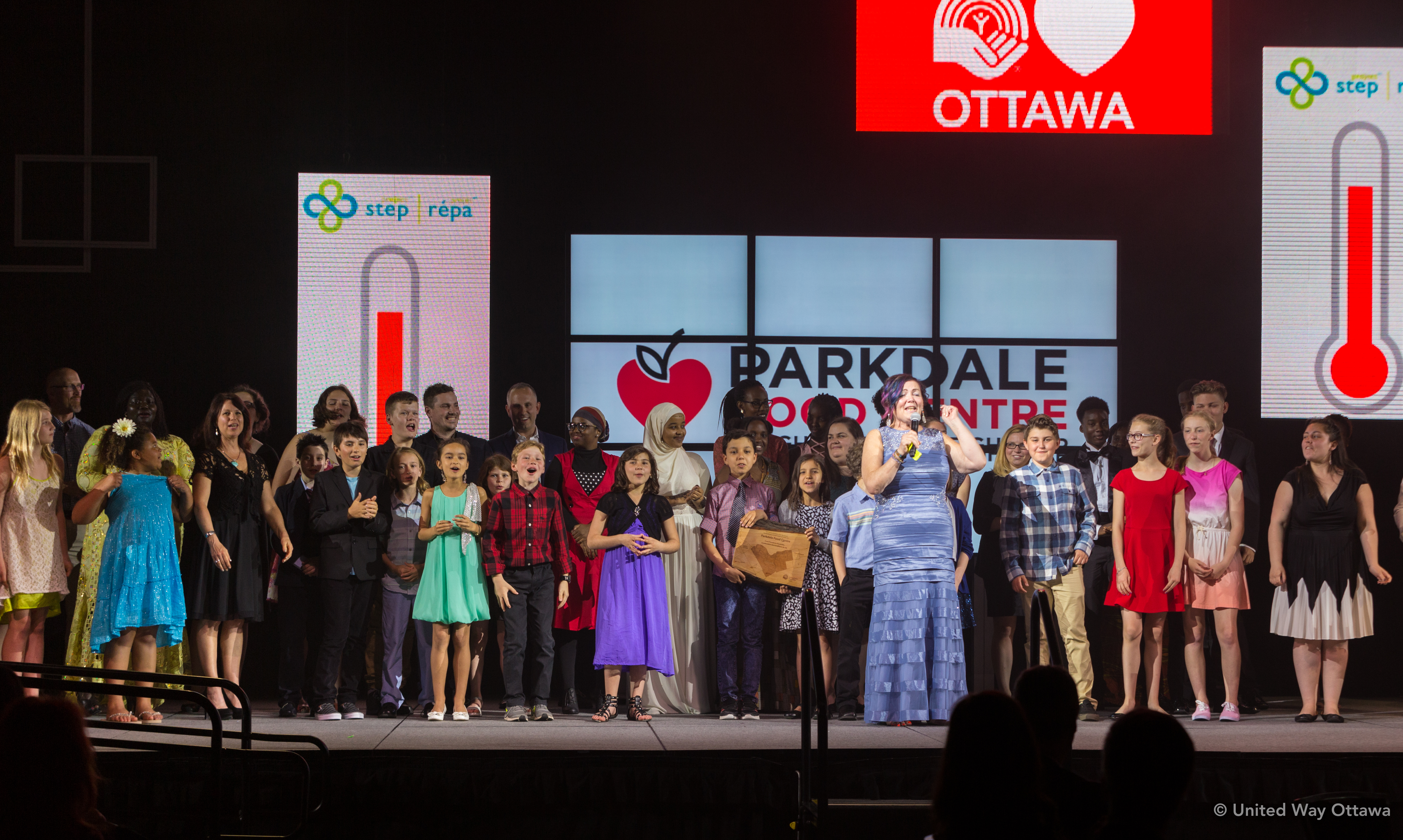 Picture of Karen Secord on stage with Parkdale Food Centre clients accepting a community builder of the year award