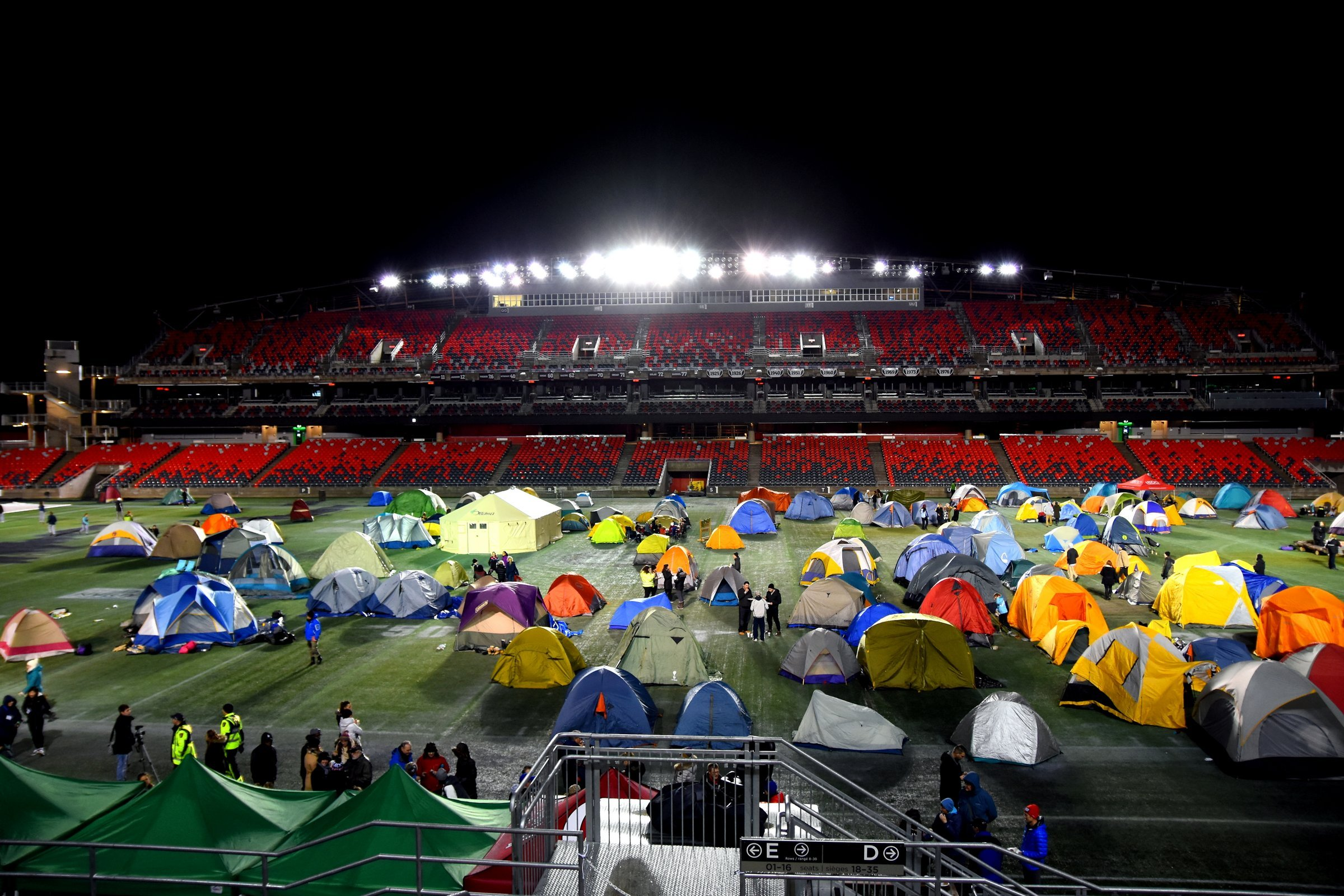 Image of a stadium with camping tents set up on the field