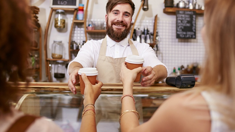 A smiling man hands two drinks over a counter.