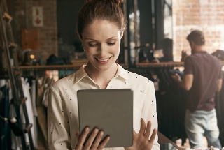 A woman smiles while using her tablet.