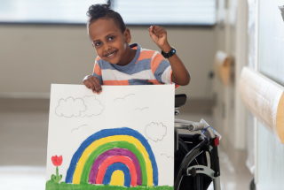 A boy using a mobility device stands smiling, holding a painting of a rainbow.